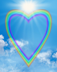 A large empty rainbow shaped heart creating a frame on a blue sky background with a big bright sunburst positioned in the cleavage of the heart