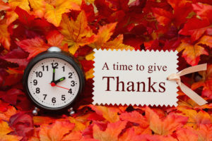 Time to give thanks message Some fall leaves and black and white alarm clock and beige gift tag with text A Time to give thanks