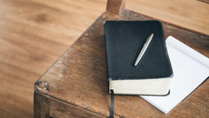 A black Bible with a pen rests over an open paper notebook on an old wooden chair. ** Note: Visible grain at 100%, best at smaller sizes